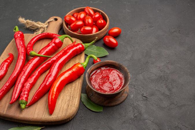 底部近距离观看砧板上的一碗樱桃西红柿 红椒 月桂叶和黑桌子上的一碗番茄酱