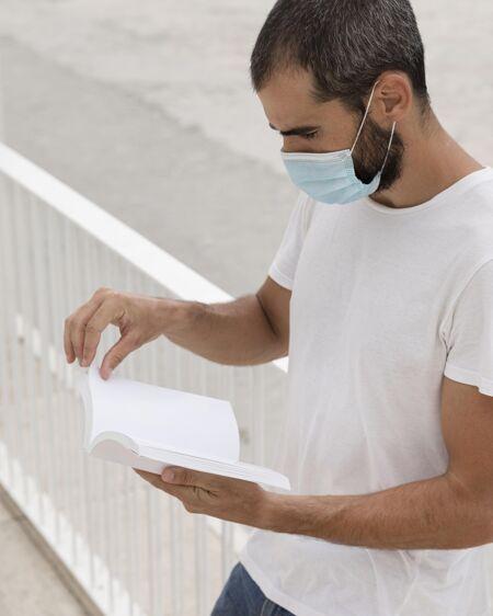 戴着面具的男人在街上看书