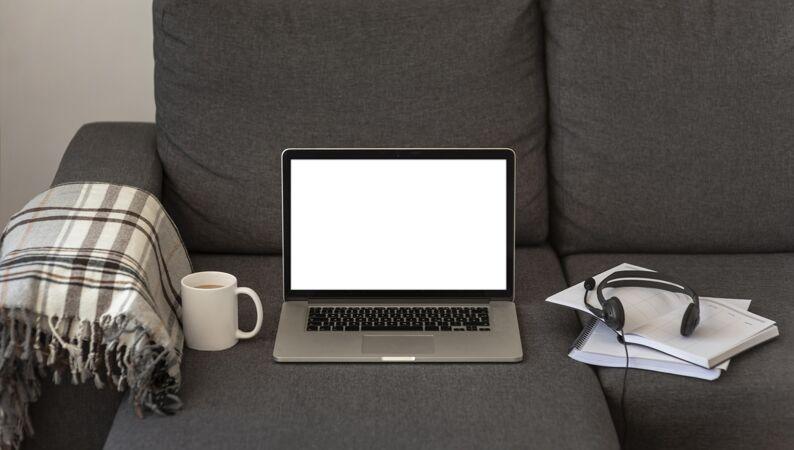 灰色沙发上的笔记本电脑模型