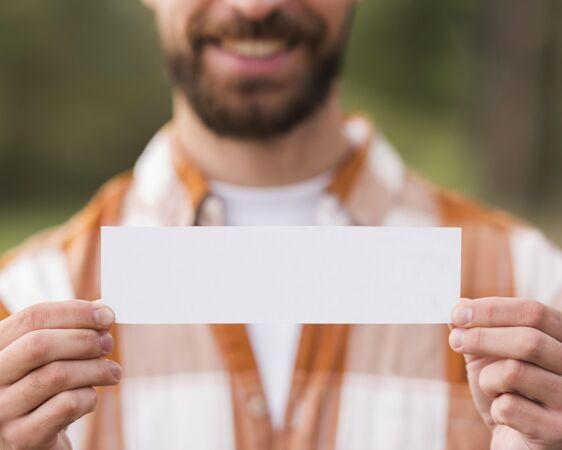 野营时笑脸男拿着一张纸的正面图